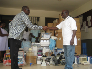 Matthew Boah presenting lab equipment and books to the Headmaster of the high school